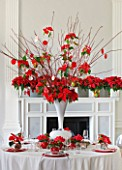 THE URBAN FLOWER FIRM (TUFF) : DINING TABLE IN WHITE SETTING DECORATED WITH WHITE VASE CENTRE PIECE FILLED WITH POINSETTIA CHRISTMAS FEELINGS RED