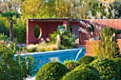 AFRICAN GARDEN  PROVENCE  FRANCE: DESIGNER DOMINIQUE LAFOURCADE: SWIMMING POOL WITH TERRACOTTA-TONED STUCCO WALLS OF THE PATIO BEHIND