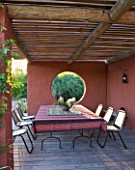 AFRICAN GARDEN  PROVENCE  FRANCE: DESIGNER DOMINIQUE LAFOURCADE: TERRACOTTA-TONED STUCCO WALLS AND DINING AREA WITH TABLE AND CHAIRS