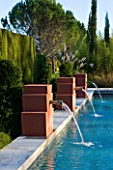 AFRICAN GARDEN  PROVENCE  FRANCE: DESIGNER DOMINIQUE LAFOURCADE: WATER FOUNTAINS SPURTING INTO THE SWIMMING POOL