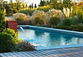 AFRICAN GARDEN  PROVENCE  FRANCE: DESIGNER DOMINIQUE LAFOURCADE: WATER FOUNTAINS SPURTING INTO THE SWIMMING POOL WITH PAMPAS GRASS  EVENING LIGHT