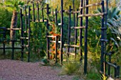 AFRICAN GARDEN  PROVENCE  FRANCE: DESIGNER DOMINIQUE LAFOURCADE: BLACK WOODEN STAKE FENCE PLANTED WITH PYRACANTHA
