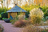 AFRICAN GARDEN  PROVENCE  FRANCE: DESIGNER DOMINIQUE LAFOURCADE: PAMPAS GRASS AND A THATCHED HUT