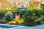 AFRICAN GARDEN  PROVENCE  FRANCE: DESIGNER DOMINIQUE LAFOURCADE: PAMPAS GRASS AND A THATCHED HUT WITH BLACKENED WOODEN STAKE FENCING
