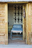 AFRICAN GARDEN  PROVENCE  FRANCE: DESIGNER DOMINIQUE LAFOURCADE: CAMP BED IN THE THATCHED HUT