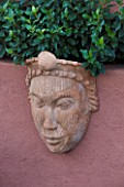 AFRICAN GARDEN  PROVENCE  FRANCE: DESIGNER DOMINIQUE LAFOURCADE: TERRACOTTA MASK ON WALL