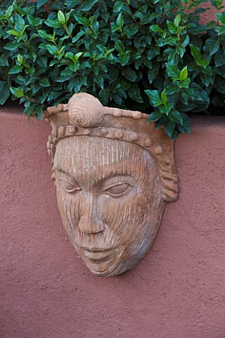 AFRICAN_GARDEN__PROVENCE__FRANCE_DESIGNER_DOMINIQUE_LAFOURCADE_TERRACOTTA_MASK_ON_WALL
