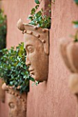 AFRICAN GARDEN  PROVENCE  FRANCE: DESIGNER DOMINIQUE LAFOURCADE: TERRACOTTA MASKS ON WALL