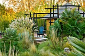 AFRICAN GARDEN  PROVENCE  FRANCE: DESIGNER DOMINIQUE LAFOURCADE: PAMPAS GRASS  THATCHED HUT AND BLACKENED WOOD FENCING