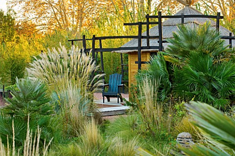 AFRICAN_GARDEN__PROVENCE__FRANCE_DESIGNER_DOMINIQUE_LAFOURCADE_PAMPAS_GRASS__THATCHED_HUT_AND_BLACKE