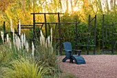 AFRICAN GARDEN  PROVENCE  FRANCE: DESIGNER DOMINIQUE LAFOURCADE: PAMPAS GRASS AND BLACKENED WOOD FENCING WITH BLACK LOUNGER/ SEAT ON ROSE COLOURED GRAVEL