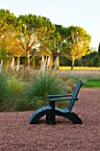 AFRICAN GARDEN  PROVENCE  FRANCE: DESIGNER DOMINIQUE LAFOURCADE: PAMPAS GRASS WITH BLACK LOUNGER/ SEAT ON ROSE COLOURED GRAVEL
