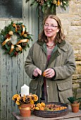 THE GARDEN AND PLANT COMPANY  HATHEROP  GLOUCESTERSHIRE: PATI WESTON WIRING DRIED ORANGES WHICH SHE USES TO DECORATE GARLANDS  WREATHS AND TABLE ARRANGEMENTS.