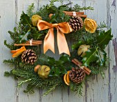 THE GARDEN AND PLANT COMPANY  HATHEROP  GLOUCESTERSHIRE: NATURAL FIR WREATH DECORATED WITH HOLLY  ROSEMARY  DRIED ORANGES  PINE CONES  CINNAMON STICKS AND CHILLI PEPPERS