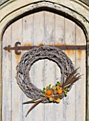 THE GARDEN AND PLANT COMPANY  HATHEROP  GLOUCESTERSHIRE: NATURAL TWIG WREATH DRESSED WITH HOLLY PINE CONES  DRIED ORANGES AND LIMES  CINNAMON  PHEASANT FEATHERS
