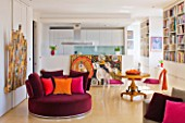 SHELLEY VON STRUNCKEL APARTMENT  LONDON: THE MAIN LIVING AREA WITH KITCHEN AT REAR AND BURGUNDY VELVET CIRCULAR SEAT