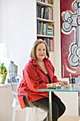 SHELLEY VON STRUNCKEL APARTMENT  LONDON: SHELLEY AT HER WRITING DESK - TWO HABITAT TABLES PUSHED TOGETHER TO FORM A SQUARE