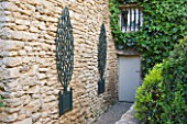GARDEN IN LUBERON  FRANCE  DESIGNED BY MICHEL SEMINI: WOODEN TROMPE LOEIL TREES IN CONTAINERS ON WALL BESIDE THE BACK DOOR