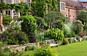 GLYNDEBOURNE, EAST SUSSEX: VIEW TO THE OPERA HOUSE OVER THE DOUBLE HERBACEOUS BORDERS WITH WHITE FOXTAIL LILIES - EREMERUS - AND EUPHORBIA - WOODEN BENCH / SEAT ON LAWN