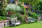 GLYNDEBOURNE, EAST SUSSEX: VIEW TO THE OPERA HOUSE OVER THE DOUBLE HERBACEOUS BORDERS WITH WHITE CRAMBE CORDIFOLIA - TWO WOODEN BENCHES / SEATS ON LAWN