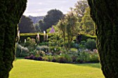 GLYNDEBOURNE, EAST SUSSEX: VIEW THROUGH YEW TREES TO LAWN AND BORDER WITH EREMURUS, ALLIUMS AND BERBERIS - BEYOND IS THE CHAMPAGNE TENT