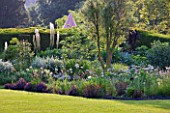 GLYNDEBOURNE, EAST SUSSEX: VIEW THROUGH YEW TREES TO LAWN AND BORDER WITH EREMURUS, ALLIUMS AND BERBERIS - BEYOND IS THE CHAMPAGNE TENT - HERBACEOUS, SUMMER