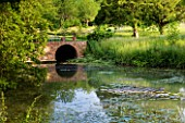 GLYNDEBOURNE, EAST SUSSEX: VIEW ACROSS LAKE TO MEADOW AND BRICK BRIDGE - WATER, POOL, TRANQUIL, PEACEFUL, COUNTRY GARDEN, LANDSCAPE