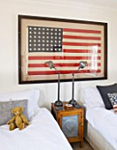 RICHARD CARNILL HOUSE  NOTTINGHAMSHIRE: TWIN GUEST ROOM. 1950S AMERICAN FLAG (48 STARS)  WOOD AND PUNCHED ZINC FRONTED CUPBOARD  LAMPS BY RALPH LAUREN HOME