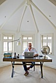 RICHARD CARNILL HOUSE  NOTTINGHAMSHIRE: CUPPOLA OFFICE: RICHARD AT DESK. DESK AND CHAIR BY B & B ITALIA MAXALTO  GLOBE BY CARNILL & COMPANY  ANGLE POISE LAMP BY ARTEMIDE FROM HEALS