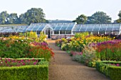 HELMSLEY WALLED GARDEN  YORKSHIRE: THE HERBACEOUS BORDER IN JULY DOMINATED BY VERBASCUMS  HELENIUMS AND ACHILLEAS  WITH GREENHOUSE BEHIND
