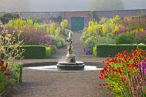 HELMSLEY_WALLED_GARDEN__YORKSHIRE_THE_HERBACEOUS_BORDER_IN_JULY_WITH_FOUNTAIN__HELENIUMS_AND_VERBASC