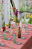 HELMSLEY WALLED GARDEN  YORKSHIRE: FLOWERS PICKED FROM THE GARDEN PLACED IN BOTTLES ON TABLE IN GREENHOUSE AND LABELLED WITH THEIR NAMES IN CHALK ON SLATE NAME TAGS