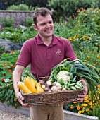 SLEDMERE HOUSE GARDEN, YORKSHIRE: HEAD GARDENER ANDY KARAVICS HOLDING BASKET OF VEGETABLES IN THE WALLED GARDEN - MAN, SUMMER, AUGUST, WORK, WORKING, PEOPLE, PERSON, MEN, JOB