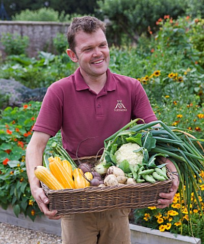 SLEDMERE_HOUSE_GARDEN_YORKSHIRE_HEAD_GARDENER_ANDY_KARAVICS_HOLDING_BASKET_OF_VEGETABLES_IN_THE_WALL