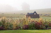 GLYNDEBOURNE, EAST SUSSEX: THE MAIN LAWN IN MIST WITH SCULPTURE IN BRONZE AND COR - TEN STEEL BY SEAN  HENRY ENTITLED CATAFALQUE, BORDER WITH SEDUMS AND GAURA LINDHEIMERI