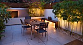 FULHAM GARDEN DESIGNED BY AMIR SCHLEZINGER - MY LANDSCAPES: MINIMALIST GARDEN LIT UP AT NIGHT -  ACER ACONITIFOLIUM  TABLE AND CHAIRS  PATIO  BUDDHA HEADS  WOODEN BENCH  BAMBOO