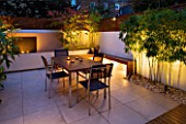 FULHAM GARDEN DESIGNED BY AMIR SCHLEZINGER - MY LANDSCAPES: MINIMALIST GARDEN LIT UP AT NIGHT -  ACER ACONITIFOLIUM  TABLE AND CHAIRS  PATIO  PHYLLOSTACHYS AUREA  WATER FEATURE