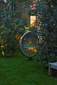 NOTTING HILL HOUSE, LONDON. GARDEN DESIGN BY BUTTER WAKEFIELD.ANTIQUE MIRROR AS FEATURE ON LAWN WITH TREE ADORNED WITH FAIRY LIGHTS. NIGHT,LIT,LIGHTING,EVENING,DUSK,GLOW,REFLECTION