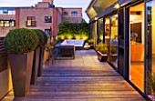 ROOF GARDEN IN SHOREDITCH  LONDON  DESIGNED BY AMIR SCHLEZINGER OF MY LANDSCAPES: DECKING  BUDDHA STATUE  DECK CHAIRS  BOX BALLS IN CONTAINERS  LIT UP AT NIGHT  LIGHTING