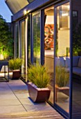 ROOF GARDEN IN SHOREDITCH  LONDON  DESIGNED BY AMIR SCHLEZINGER OF MY LANDSCAPES: DECKING AND CONTAINERS WITH LIBERTIA GOLDFINGER  LIT UP AT NIGHT  LIGHTING