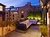 ROOF GARDEN IN SHOREDITCH  LONDON  DESIGNED BY AMIR SCHLEZINGER OF MY LANDSCAPES: A PLACE TO SIT: LOUNGER ON TERRACE/ PATIO WITH STIPA TENUISSIMA. LIT UP AT NIGHT  LIGHTING