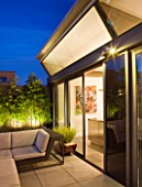 ROOF GARDEN IN SHOREDITCH  LONDON  DESIGNED BY AMIR SCHLEZINGER OF MY LANDSCAPES: PATIO WITH LOUNGER  PHYLLOSTACHYS NIGRA   LIT UP AT NIGHT  LIGHTING