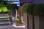ROOF GARDEN IN SHOREDITCH  LONDON  DESIGNED BY AMIR SCHLEZINGER OF MY LANDSCAPES: DECKING WITH BUDDHA STATUE AND CONTAINERS WITH BOX BALLS  LIT UP AT NIGHT. LIGHTING