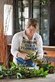 COMMON FARM FLOWERS. SOMERSET: GEORGIE NEWBERY  FOUNDER AND OWNER OF COMMON FARM FLOWERS  MAKES A BRITISH GROWN SEASONAL FOLIAGE GARLAND WITH LAUREL  HOLLY AND VIBURNUM DAVIDII