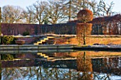 BROUGHTON GRANGE, OXFORDSHIRE: DESIGNER TOM STUART - SMITH: CLIPPED TOPIARY BEECH HEDGE IN FROST IN THE WALLED GARDEN. WINTER, COUNTRY GARDEN, TRIMMED, HEDGING, WATER, POOL, POND