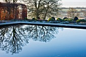 BROUGHTON GRANGE, OXFORDSHIRE: DESIGNER TOM STUART - SMITH: BEECH HEDGES IN FROST IN THE WALLED GARDEN WITH REFLECTIONS ON WATER. WINTER, COUNTRY GARDEN, TRIMMED, POOL, LAKE, POND