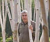 ANGLESEY ABBEY  CAMBRIDGESHIRE: HEAD GARDENER RICHARD RICHARD TODD AMONGST THE GROVE OF BIRCH TREES - BETULA UTILIS VAR. JACQUEMONTII IN THE WINTER GARDEN