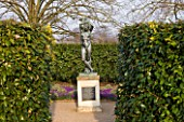 ANGLESEY ABBEY  CAMBRIDGESHIRE: STATUE - THE BOY WITH RAISED ARMS IN A SMALL ENCLOSED GARDEN