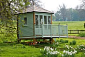 EASTON WALLED GARDEN  LINCOLNSHIRE: BEAUTIFUL PAINTED WOODEN SUMMERHOUSE WITH DRIFTS OF NARCISSUS POETICUS RECURVUS IN THE MEADOW. RETREAT  GARDEN BUILDING.SPRING  FLOWERS