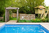 ARALIA GARDEN DESIGN - PATRICIA FOX: WEDNESDAY HOUSE: SWIMMING POOL AND WOODEN PERGOLA, TREE HOUSE IN BACKGROUND